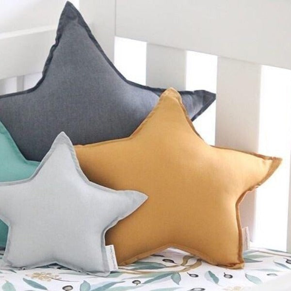 cot filled with bright coloured star cushions in babys room