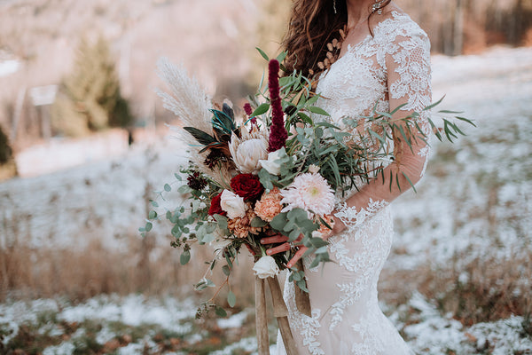 woman standing in a field dusted with snow in a white lace dress holding an asymmetrical bouquet featuring roses, protea, eucalyptus, and pampas grass