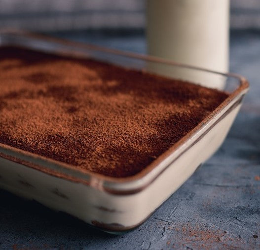 Sifted dutch cocoa falls to make a soft layer atop a homemade tiramisu