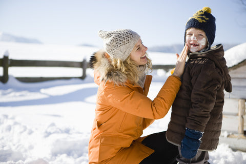 mother applying spf protection sunscreen to son
