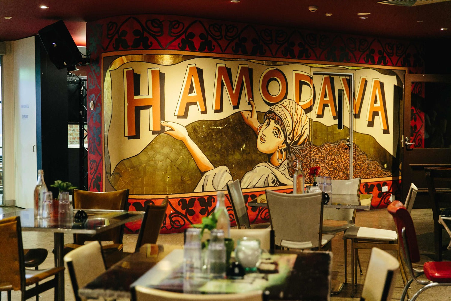 Image of the cafe hamodava. Chairs, tables and a beautiful wall art piece with the word Hamodava.
