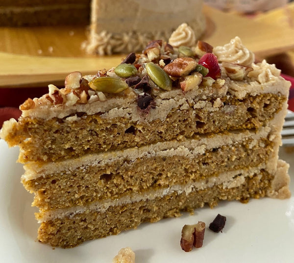 Spiced pumpkin cake layered with vegan maple butter cream, topped with toasted pecans, pumpkin seeds, chopped chocolate, and pomegranate seeds.