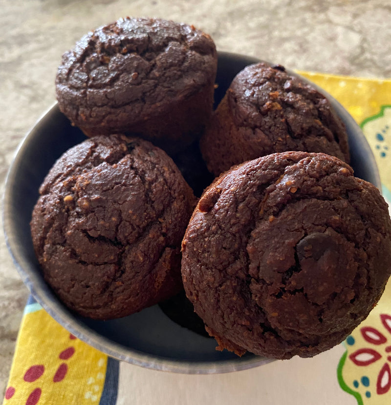 Moist and fluffy zucchini double chocolate muffins nestled in a ceramic bowl.