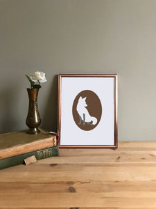 Fox cameo art print on white paper shown in copper frame on table with vase