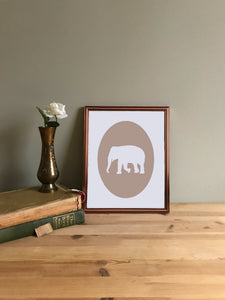 Tan elephant giclee cameo art print on white fine art paper shown in copper frame on table