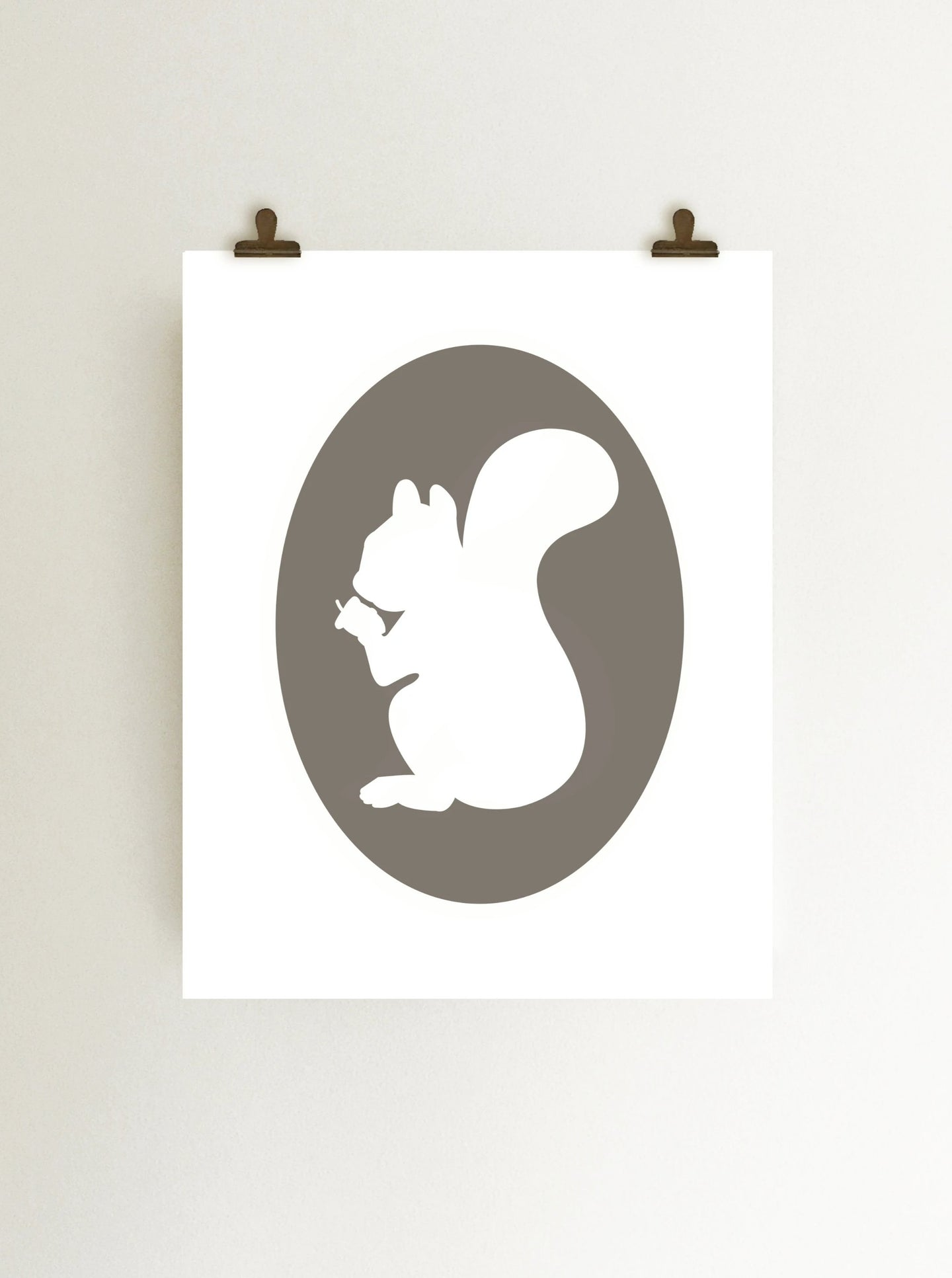Gray squirrel holding acorn cameo art print, giclee on white fine art print paper shown hanging on wall from clips