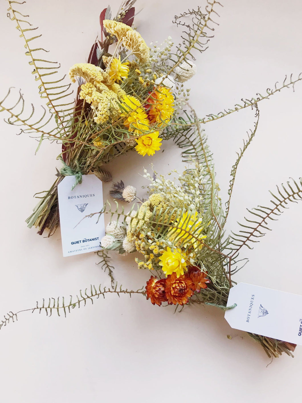 A dried flower bouquet made with yarrow, strawflower, globe amaranth, sea star fern, pepper grass and tansy. A bright yellow bouquet.
