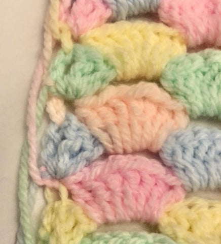 Pastel Shells - Coloured yarn strands taking up the side of the blanket.