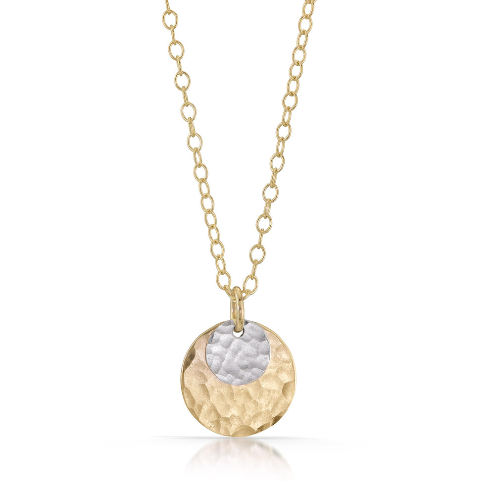 Small silver disc on top of large gold disc necklace.