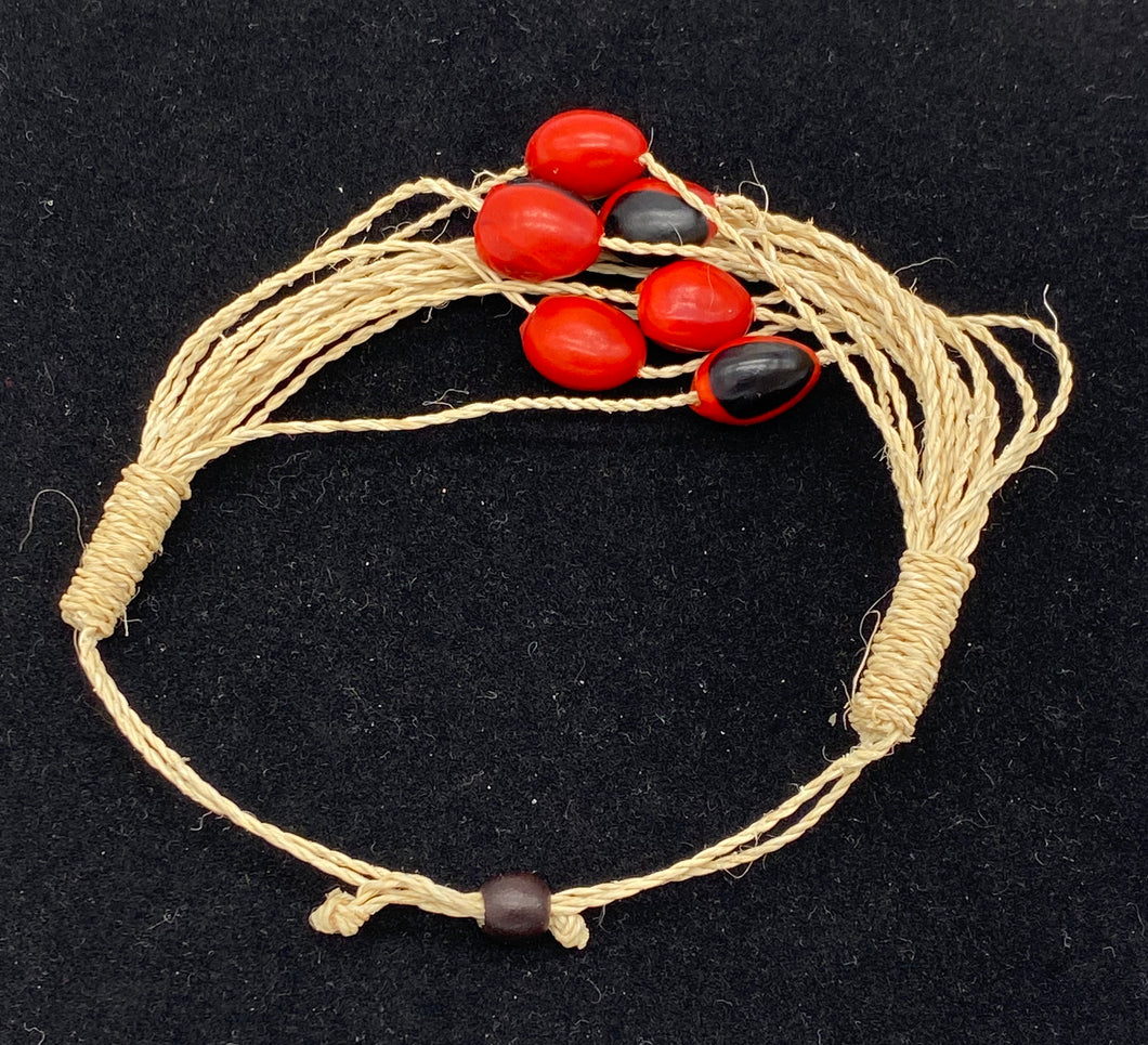 Woven strand bracelet with red and black seeds
