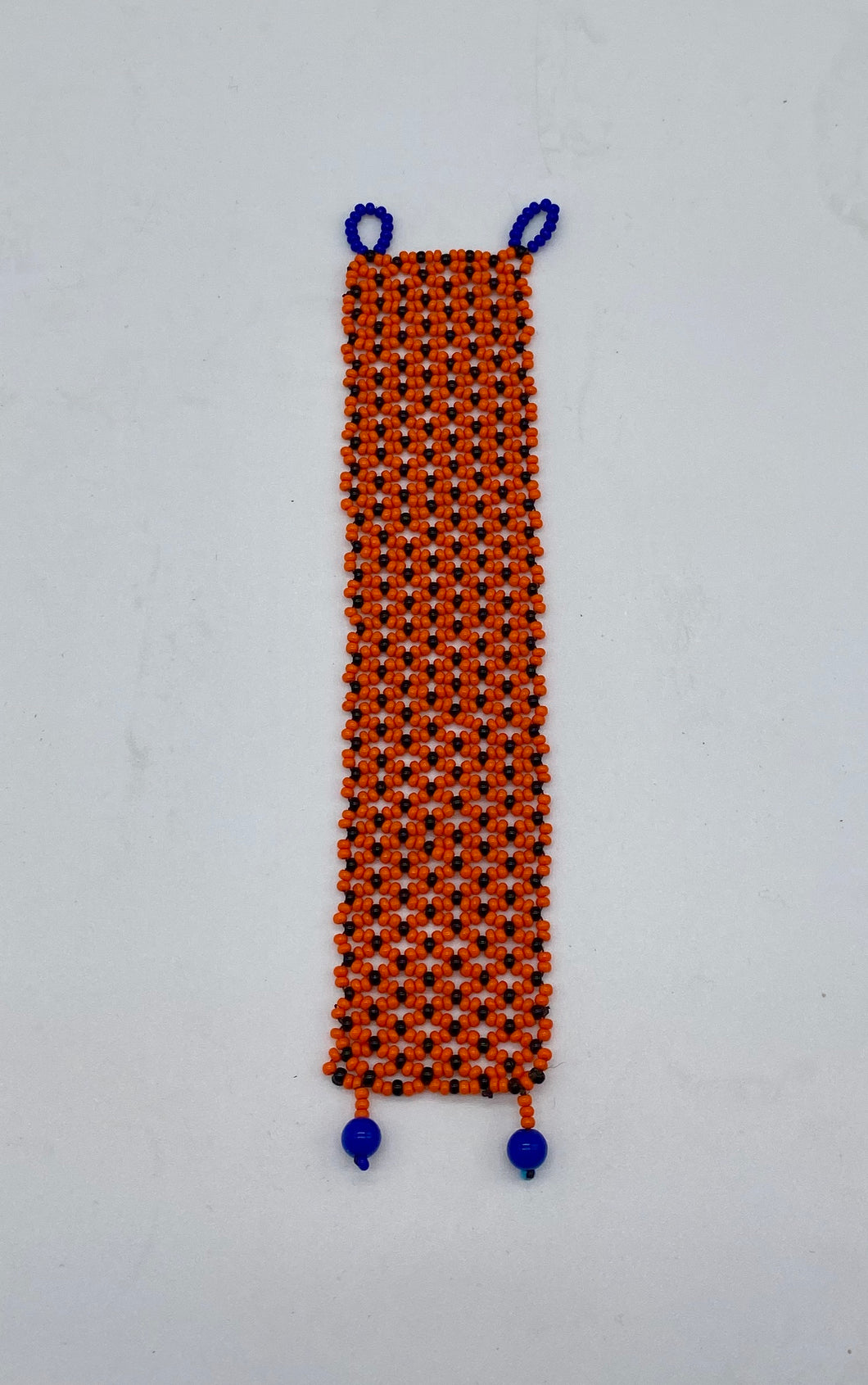 Delicate orange bracelet with blue clasps