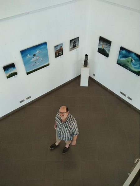 Portrait of Jon Everitt in an exhibition of his paintings
