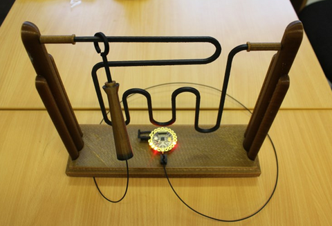 Photograph of a buzz trace game 3D printed using conductive filament. A small circuit and light sits on the base of the game, showing that the filament is connected to a power source.