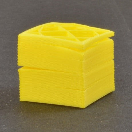 A small cubic test print exhibiting significant layer shifting and separation.