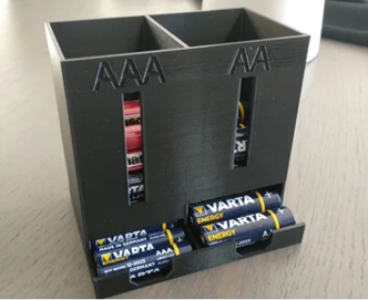 A 3D printed battery holder and dispenser that stands upright on a table. On the left, there is a container and dispenser for triple-A batteries. On the right, a container and dispenser of the same size is joined for double-A batteries.