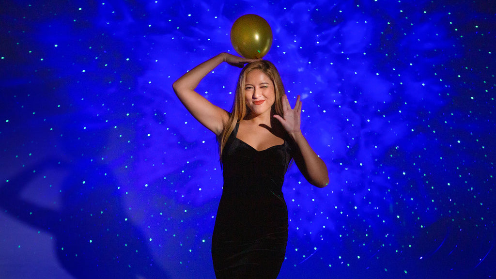 woman posing with balloon in front of sky lite galaxy projector