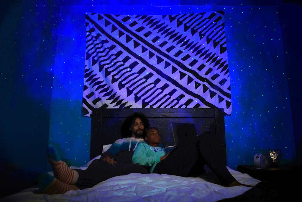 couple watching netflix under galaxy lights