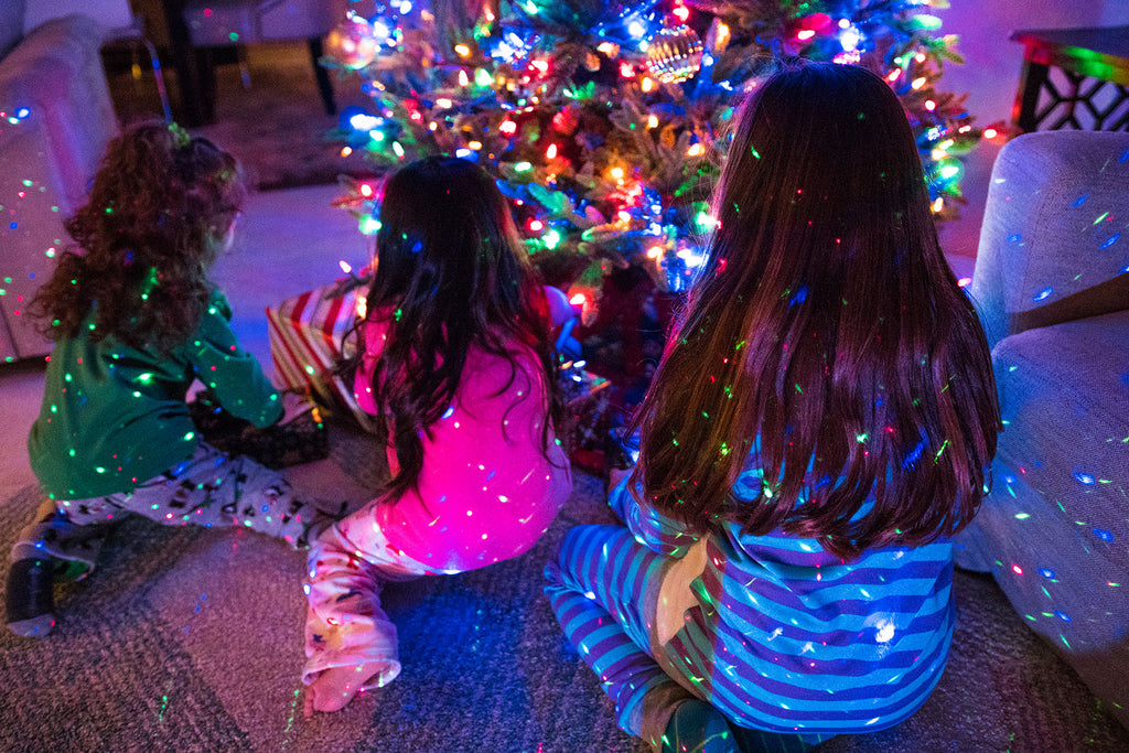 children opening christmas presents with christmas lights