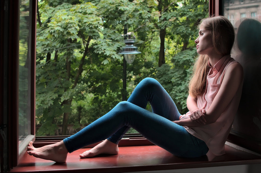 woman at window looking out at peaceful nature view