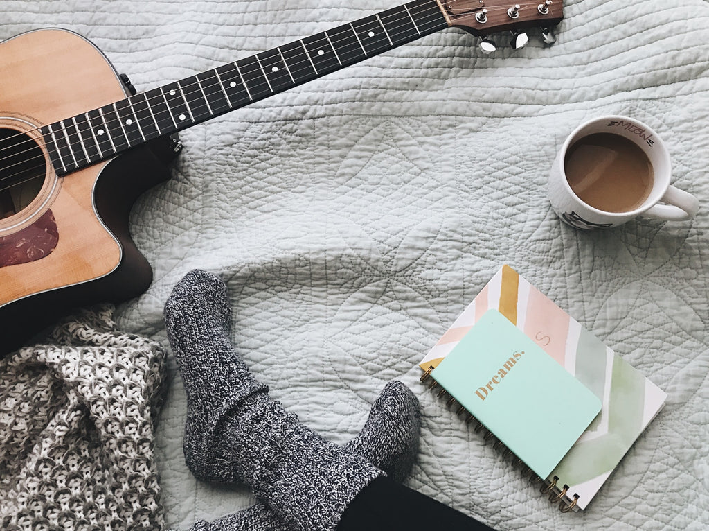 cozy bedroom with guitar and soft blankets