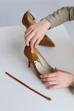 Image of ankle strap being firmly pressed against high heel shoe to demonstrate how to attach the ankle strap