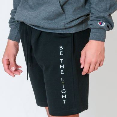 Black Fleece Shorts with Be the Light in White Text Down the Left Thigh
