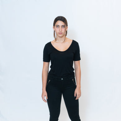 Deep scoop neck black t-shirt with Ari Arteaga's red heart on the left shoulder