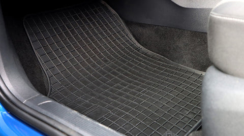 Black rubber car mat placed in the footwell of a car.