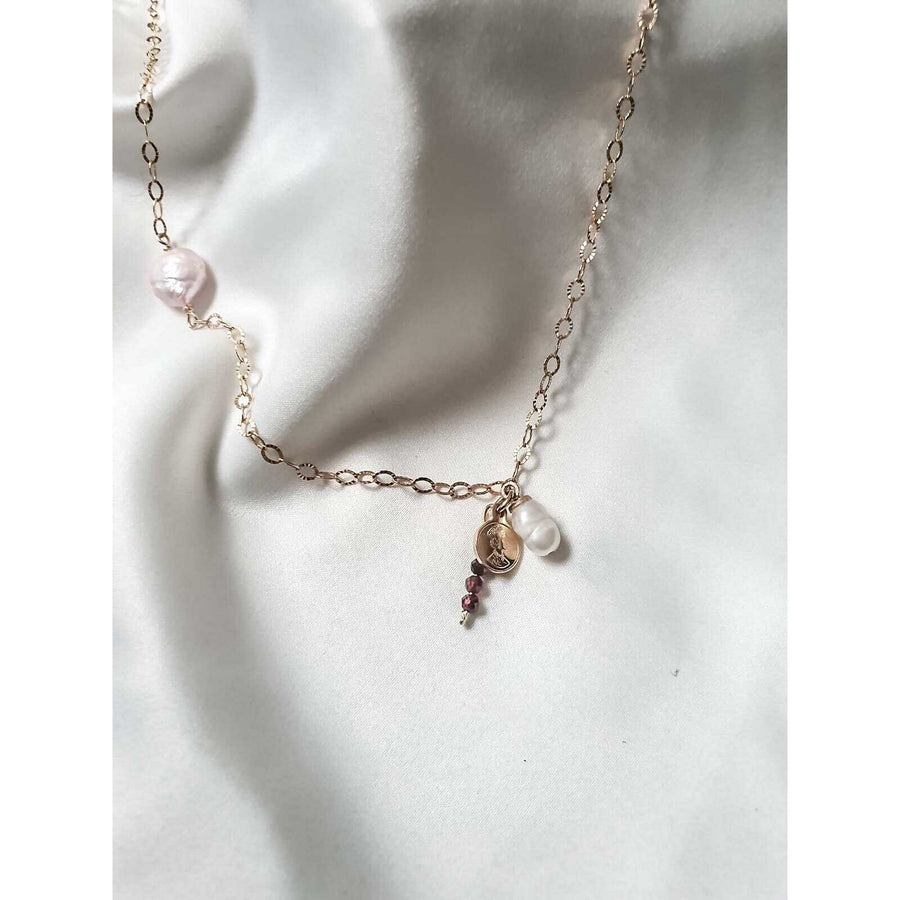 A gold necklace with a pink pearl, a pendant of white pearl and a garnet