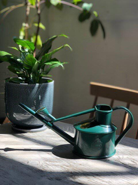haws green watering can on the table
