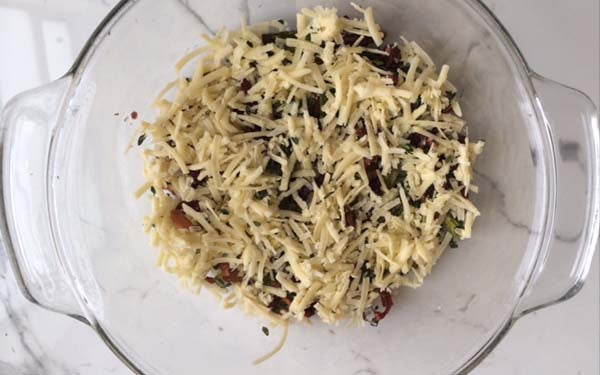 In a 2-quart round Pyrex glass baking dish (3-inches high and 9.5- inches in diameter), sprinkle asparagus, lemon thyme, sun-dried tomatoes, bacon, and minced chives on bottom, then sprinkle 3/4 cup of grated cheese over veggie/bacon mixture.