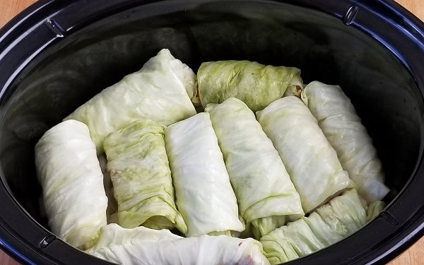 Build layers of flavor in the crockpot for the cook. The first layer consists of half of the onions and sauerkraut. Then place a single layer of all the cabbage rolls over this sauerkraut mixture.