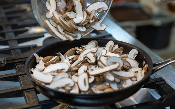 Slice mushrooms. Heat 2 tablespoons of the oil in a large sauté pan over medium high heat.