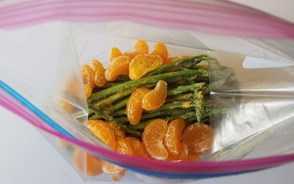 Place asparagus, tangerine segments, olive oil, lemon pepper and salt in a large sealable plastic freezer bag and shake until evenly coated.
