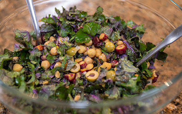 In a large bowl add the kale sprouts, garbanzo beans, watermelon radishes, carrots, and olives, and toss to combine. Add the beets and avocado on top. Sprinkle on the pepitas. Drizzle the dressing over the salad. Lightly toss to combine, and serve.