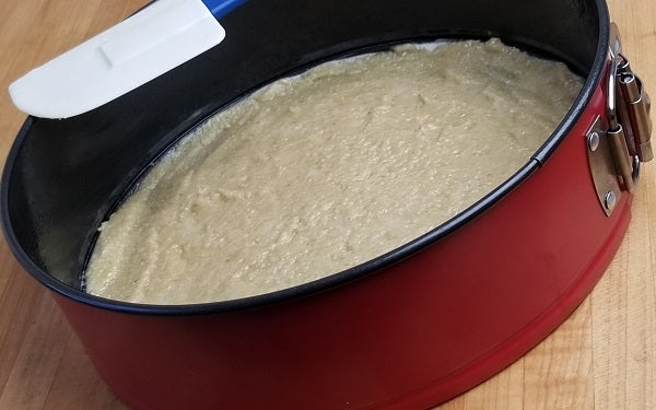 Spread macadamia mixture over the bottom of a greased cheesecake pan, cover with waxed or parchment paper, then press down until evenly distributed. Set aside.