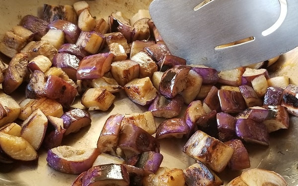 Heat half the oil in a wide pan until white wisps of smoke appear. Sauté the eggplant in two batches; if pan is too crowded, the eggplant will tend to steam instead of fry.
