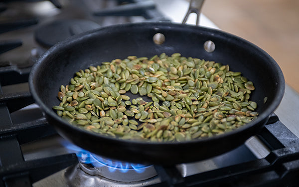 In a dry skillet, lightly toast the pumpkin seeds over medium low heat, stirring regularly, until they smell toasty and just start to change color and pop, approximately 7 minutes.