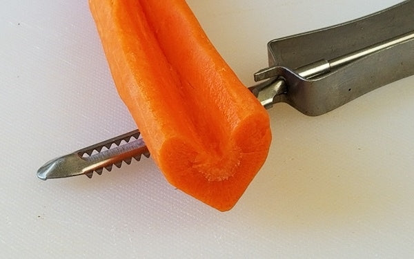 Using a potato peeler have your kitchen helpers peel the outer skin of each carrot. Then, with the same peeler, gently round off the pointed edges of both sides of the notch all the way down the carrot.