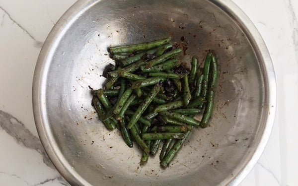 Squeeze 1½ heads of black garlic cloves from cut heads over green beans, then micro plane fresh garlic, sprinkle red pepper flakes and drizzle olive oil over veggies and gently toss to combine.