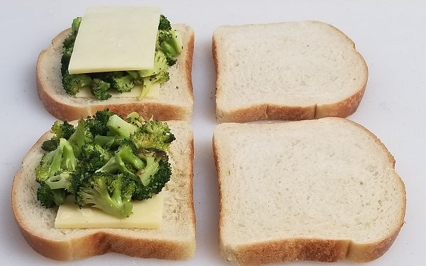 Dividing the ingredients evenly, layer cheese on the one side of half of the bread slices, then cover cheese with chopped broccoli.