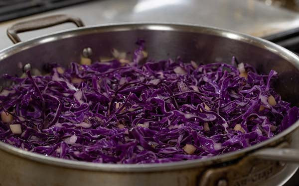 Add the cabbage, toss well. Drizzle the vinegar over the cabbage, cover and simmer for about 5 minutes. Toss well.