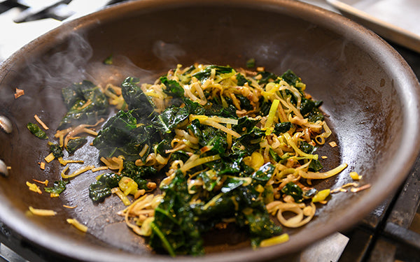 Caramelize the leeks and garlic in the olive oil for about 4 to 5 minutes. Add the chopped kale and sauté until tender. Set aside.