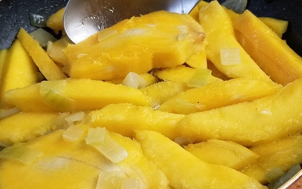Peel and pit the mangoes, cut them into long slices. Sauté onion in olive oil until translucent, then add the mango slices and continue the sauté.