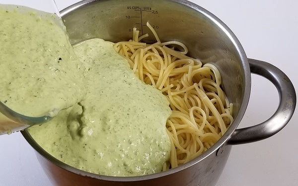 Image of adding sauce to spaghetti noodles