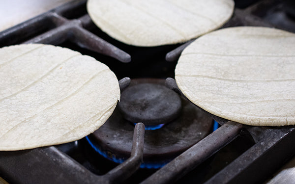 Take the corn tortillas, one at a time, and heat over an open flame/gas burner about 15 seconds per side.
