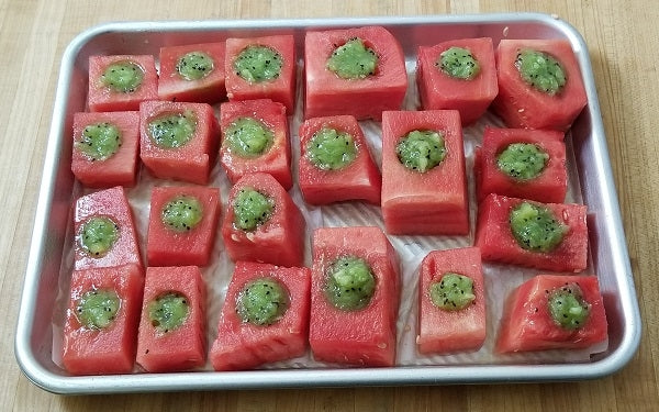 Place watermelon cubes on a cookie tray lined with parchment paper, then fill each cup with kiwi purée.