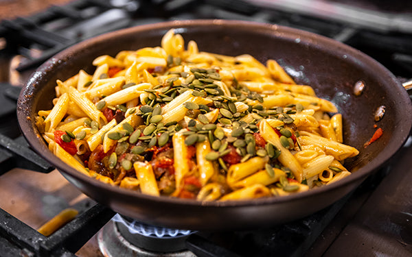 Add the penne pasta and the toasted pepitas to the sauce and toss to combine.