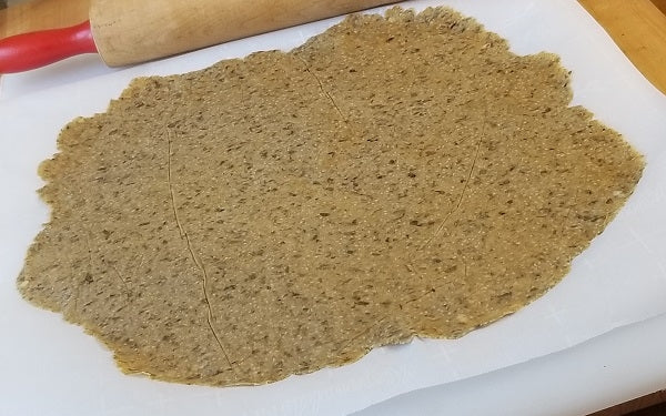 Divide dough into 2 portions. Place a large sheet of parchment paper on a cutting board, center one portion of dough on the paper then lay another sheet of parchment on top.