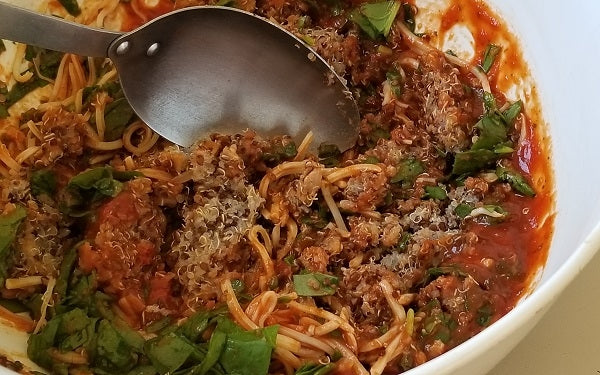 Combine quinoa, marinara sauce, chopped spinach, and a ¼ cup of the cheese in a mixing bowl.
